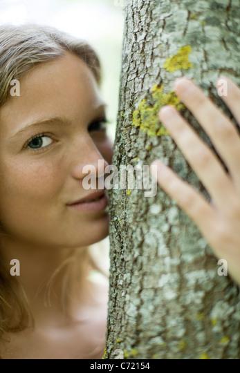 Junge Frau umarmt Baum, Porträt Stockbild