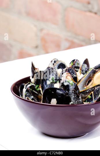 Schale mit Muscheln mit Sahne-Sauce auf weiße Tischdecke Stockbild