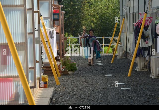 Eine Frau sammelt die Wäsche in einer Notunterkunft in Toni fast ein halbes Jahr nach der schlimmsten Katastrophe Stockbild