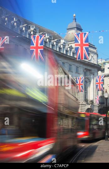 Rote Busse und Union Jack-Flaggen in der Regent Street; London; England Stockbild