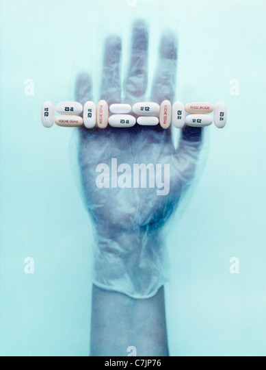 Behandschuhte Hand, die Pillen Stockbild