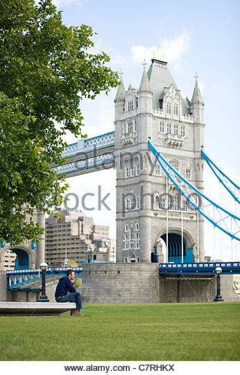 Einen mittleren Erwachsenenalter Mann sitzt in der Nähe von Tower Bridge, telefonieren mit einem Handy Stockbild