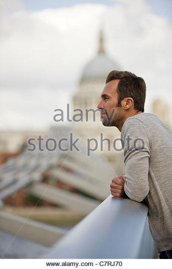 Ein Mid-Adult-Mann steht auf die Millennium Bridge, bewundern Sie die Aussicht Stockbild