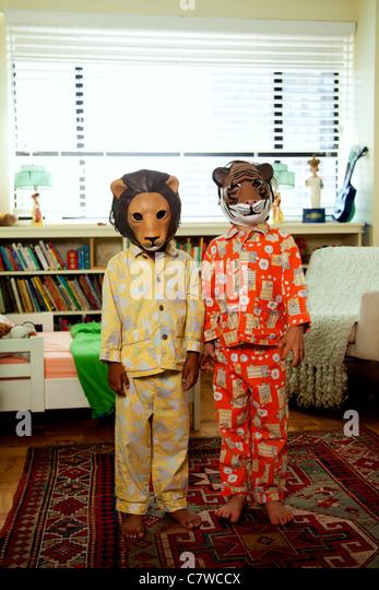 Zwei Kinder mit Masken auf im Pyjama Stockbild