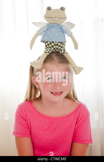junges Mädchen mit Spielzeug Frosch auf Kopf Stockbild