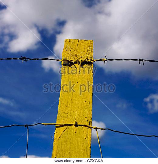 Gelbe Post, Stacheldraht, gegen blauen Himmel mit Wolken Stockbild