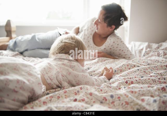 Kleinkind Mädchen mit Mutter im Bett sitzen Stockbild