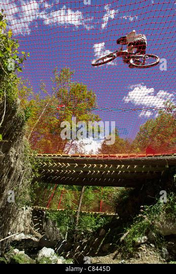 Mountainbiker auf Verrechnung über Graben Stockbild