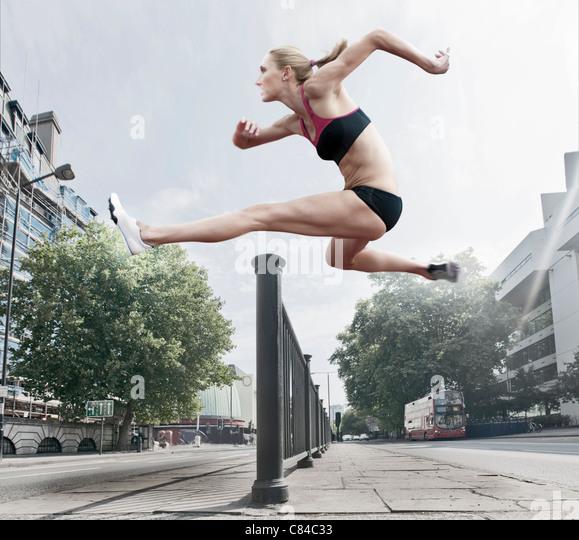 Athleten springen über Geländer auf Straße Stockbild