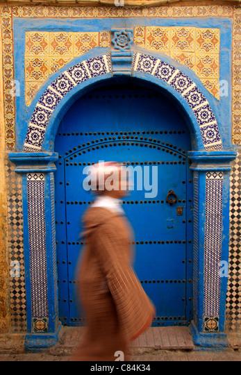 Junge Frau trägt ein Jellabah geht vorbei an einer dekorativen hölzernen & geflieste Tür in der Stockbild