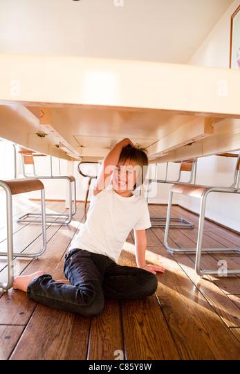 Junge sitzt unter Esstisch Stockbild