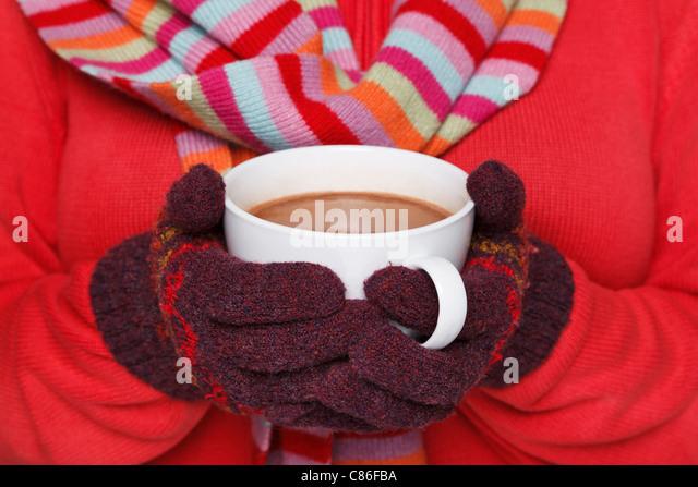 TRIKOTSHIRT Foto einer Frau trägt einen roten Pullover, wollene Handschuhe und Schal hält eine Tasse heiße Stockbild