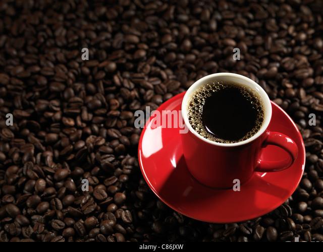 Rote Tasse Kaffee mit einer Untertasse auf Kaffeebohne Hintergrund Stockbild