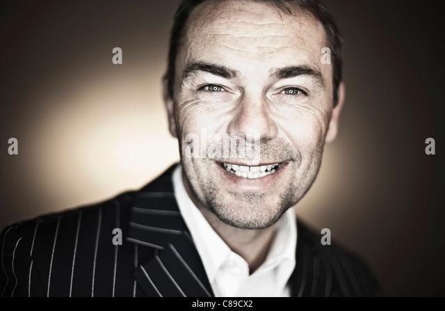 Nahaufnahme von reifer Mann in Anzug vor schwarzem Hintergrund, Lächeln, Porträt Stockbild