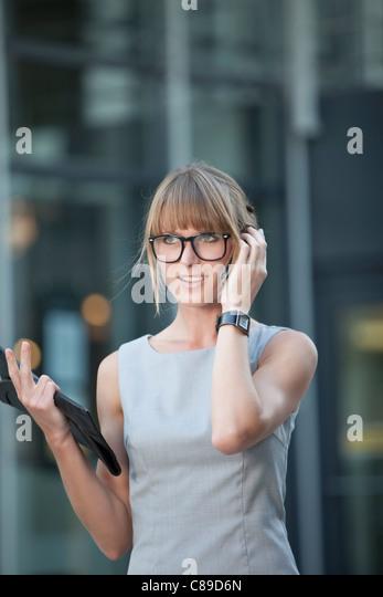 Deutschland, Bayern, München, junge Geschäftsfrau mit Brille mit Handy Stockbild