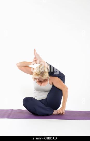 Frau sitzt in Yoga-Haltung Stockbild