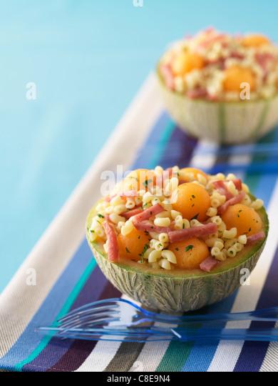 Muschel-Nudeln, Melone und rohem Schinken Salat serviert in einer Melone Stockbild