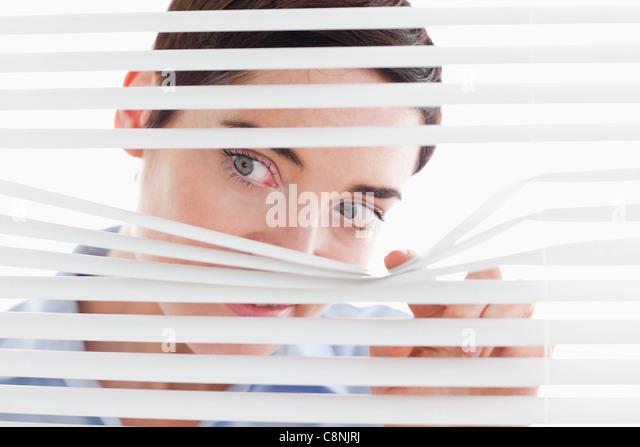 Niedliche Geschäftsfrau spähen durch eine Jalousie Stockbild