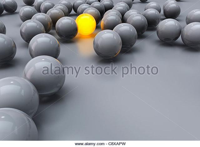 Leuchtende gelbe Kugel unter grauen Kugeln Stockbild