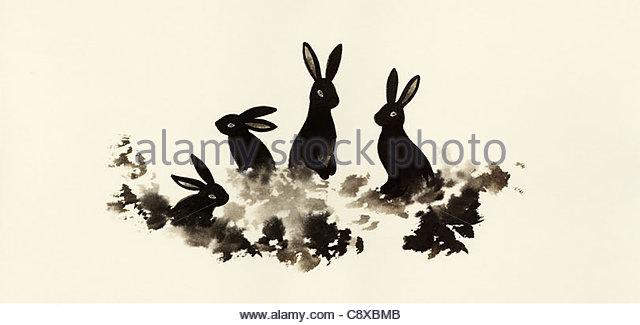 Kaninchen im Rasen zusammensitzen Stockbild