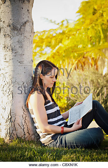 USA, California, Lawndale, Frau sitzt unter Baum lesen Zeitung Stockbild