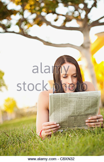 USA, California, Lawndale, Frau liegt auf dem Rasen, die Zeitung lesen Stockbild