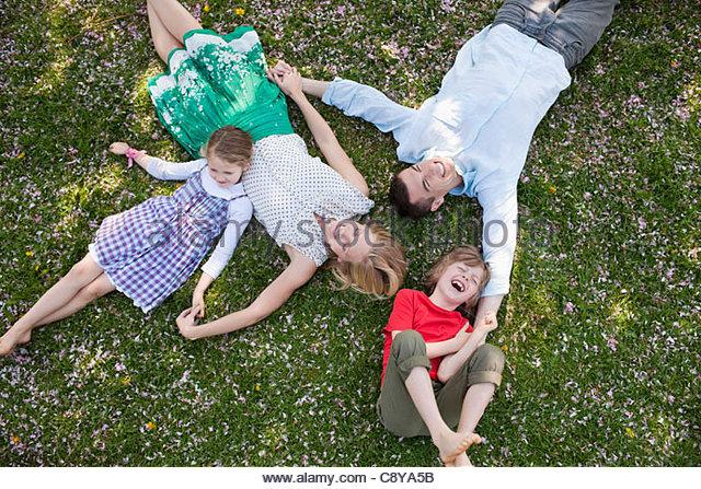 Familie Verlegung Gras zusammen Stockbild