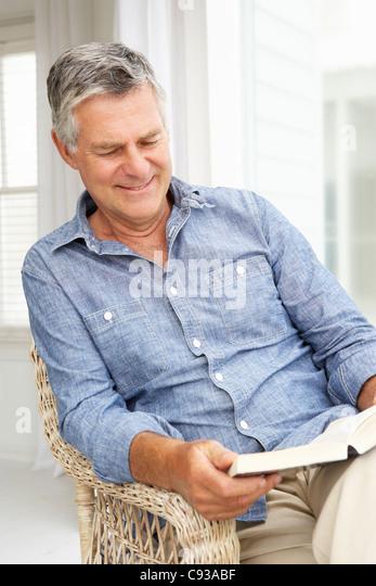 Ältere Mann zu Hause entspannen mit einem Buch Stockbild