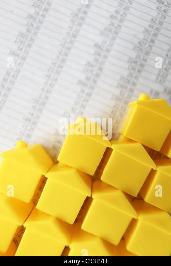 Kleine Kunststoff-Häuser in einem Arbeitsblatt Stockbild
