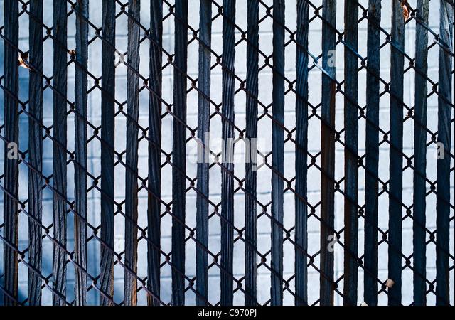 Zaun mit Holzlatten bei starker Sonneneinstrahlung Stockbild