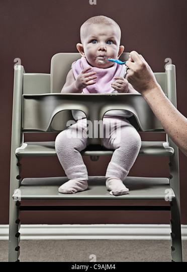 Vier Monate altes Mädchen essen erste Babynahrung im Hochstuhl Stockbild
