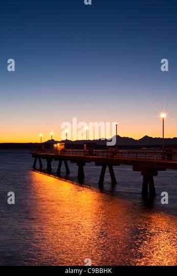 Silhouette Pier mit Menschen Angeln Dock bei Sonnenuntergang am Puget Sound mit Olympic mountains Stockbild