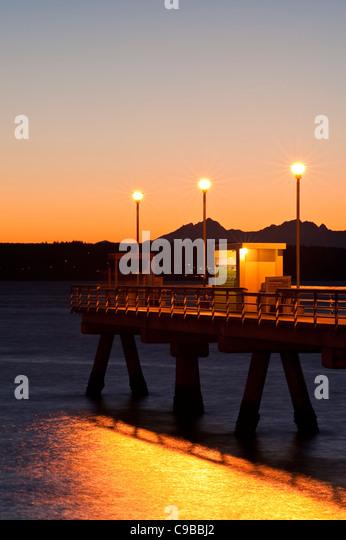 Silhouette Pier mit Menschen Angeln Dock bei Sonnenuntergang am Puget Sound mit Olympic Mountains Edmonds Washington Stockbild