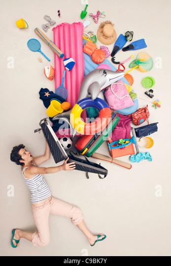 Deutschland, künstliche Szene mit Frau öffnen Gepäck voller Spielzeug für den Strand Stockbild