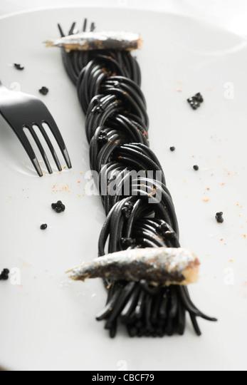 Schwarze Spaghetti mit Sardinen und Espelette Pfeffer Stockbild