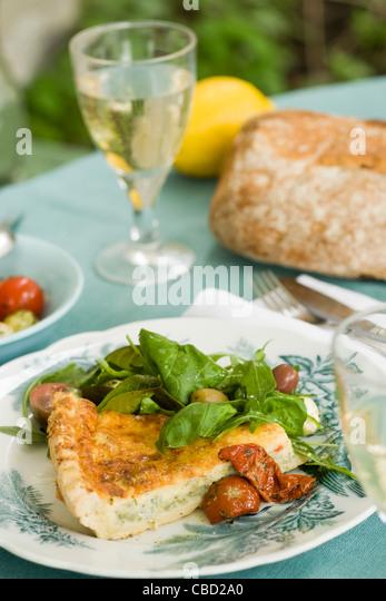 Quiche serviert mit Salat Stockbild
