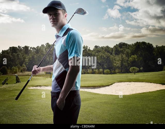 Mann trägt Golfclub auf Kurs Stockbild