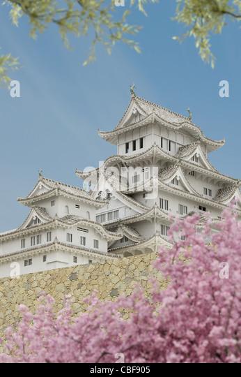 Japanische Pagode Gebäude, gesehen von einem niedrigeren Niveau, mit Pflanzen im Vordergrund. Stockbild