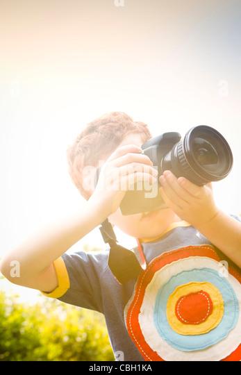 Ein kleiner Junge im Alter von 7, mit einer digitalen SLR-Kamera in einem sonnigen Garten. Stockbild