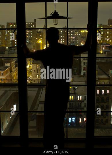 Silhouette der Mann am Fenster in der Nacht mit Blick auf Nw York City, New York, USA Stockbild