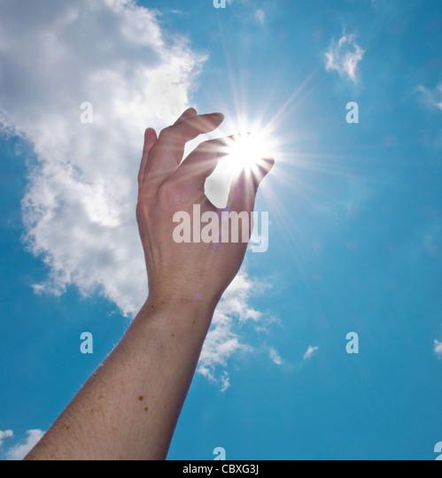 einer Hand fangen die Sonne am blauen Himmel Stockbild
