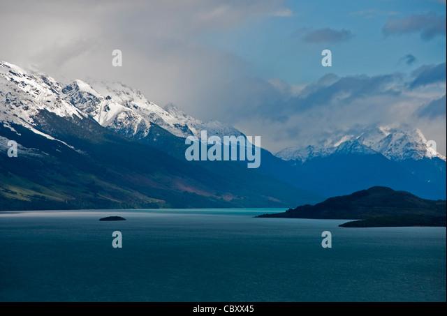 Wolken im zeitigen Frühjahr über Lake Wakatipu und die Berge in der Nähe von Queenstown, Neuseeland Stockbild