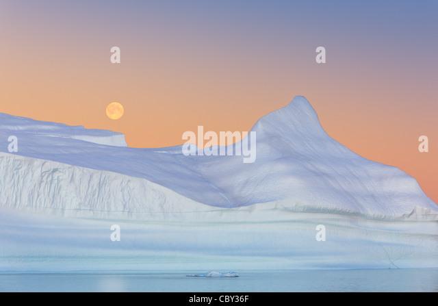 Eisberg bei Sonnenuntergang und Mondaufgang am Hall Bredning, Scoresbysund, Grönland Stockbild
