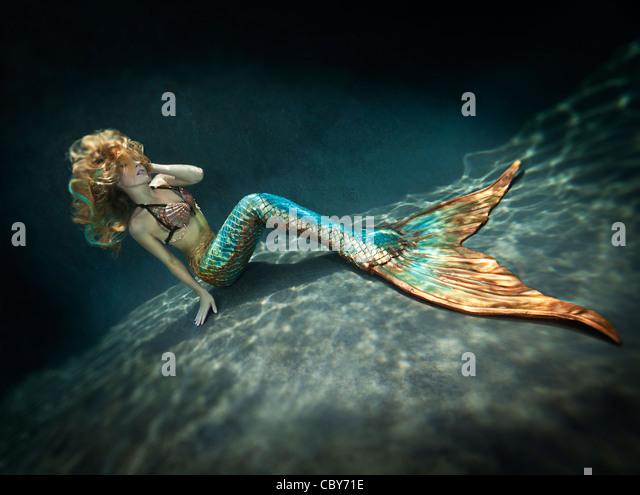 Meerjungfrau sitzt allein Unterwasser Stockbild