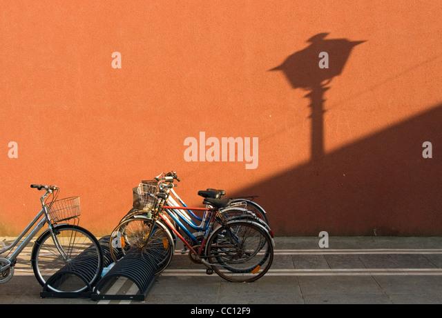 Straßenszene mit Fahrrädern und bunt bemalte Wand, historische Zentrum von Caorle, Veneto, Italien Stockbild