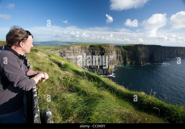 Touristen genießen den Blick auf die Cliffs of Moher, Burren, County Clare, Irland. Stockbild