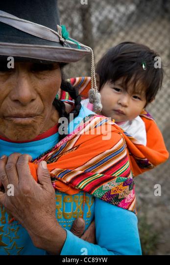 Eine Frau trägt ein Baby auf dem Rücken in einem Armenviertel von Lima, Peru, Südamerika. Stockbild