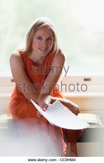 Porträt von lächelnden Frau Holding Noten in der Nähe von Fenster Stockbild