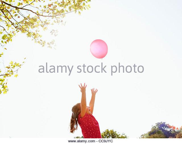 Mädchen für roten Ballon in sonnigen Himmel erreichen Stockbild