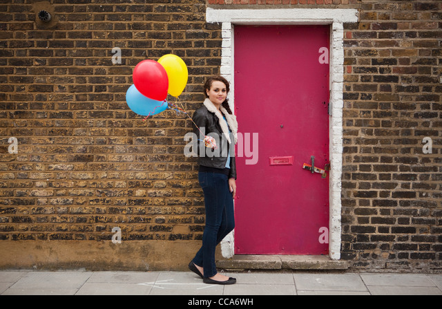 Junge Frau mit bunten Luftballons gegen Mauer Stockbild